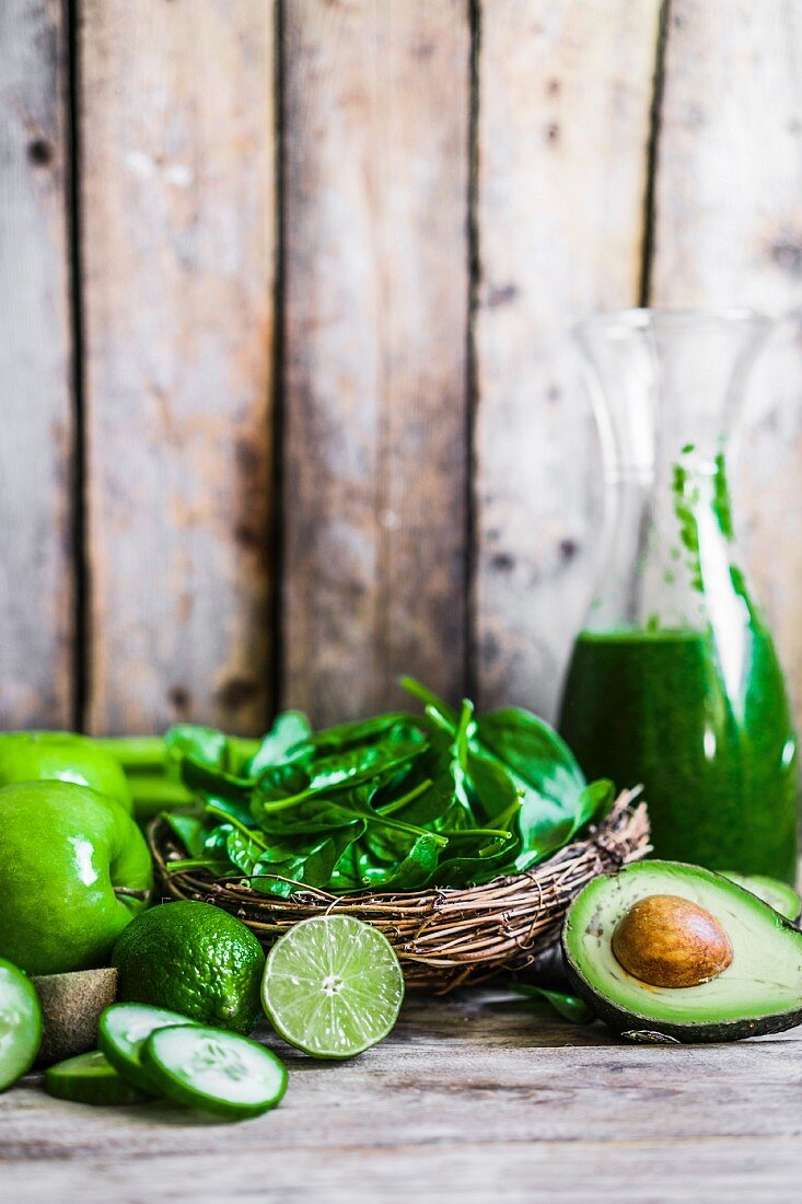 Ingredients for green smoothies on a rustic wooden surface