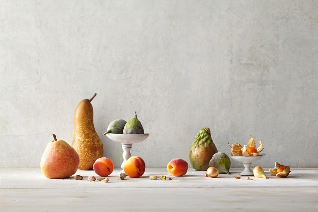 An arrangement of fruit featuring pears, apricots, pistachios, figs, pearl onions, prickly pears and physalis