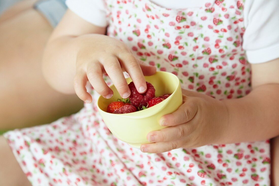 A child with a bowl of fresh berries