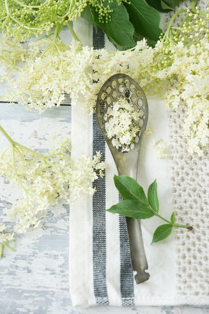 A draining spoon and elderflowers
