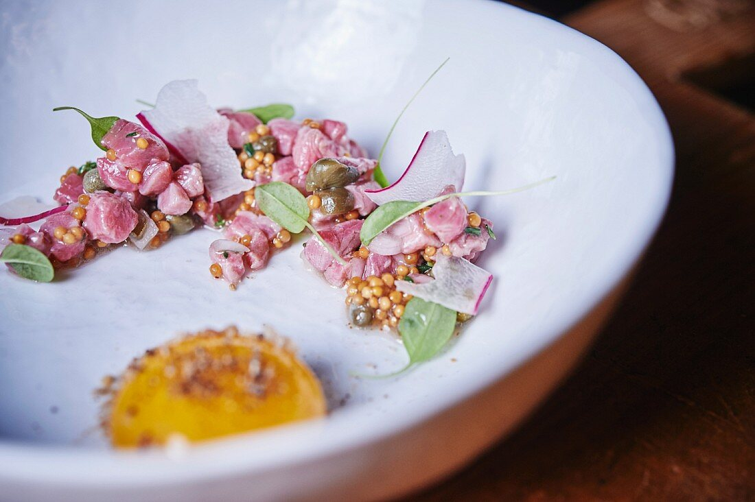 Beef tatar withcress, pickled radish, mustard seeds and an egg yolk with toasted breadcrumbs