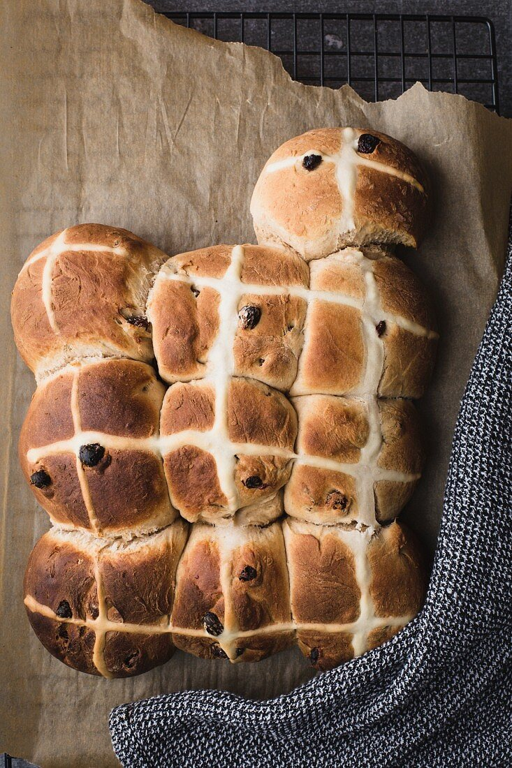 Freshly baked hot cross buns on a piece of baking paper (seen from above)