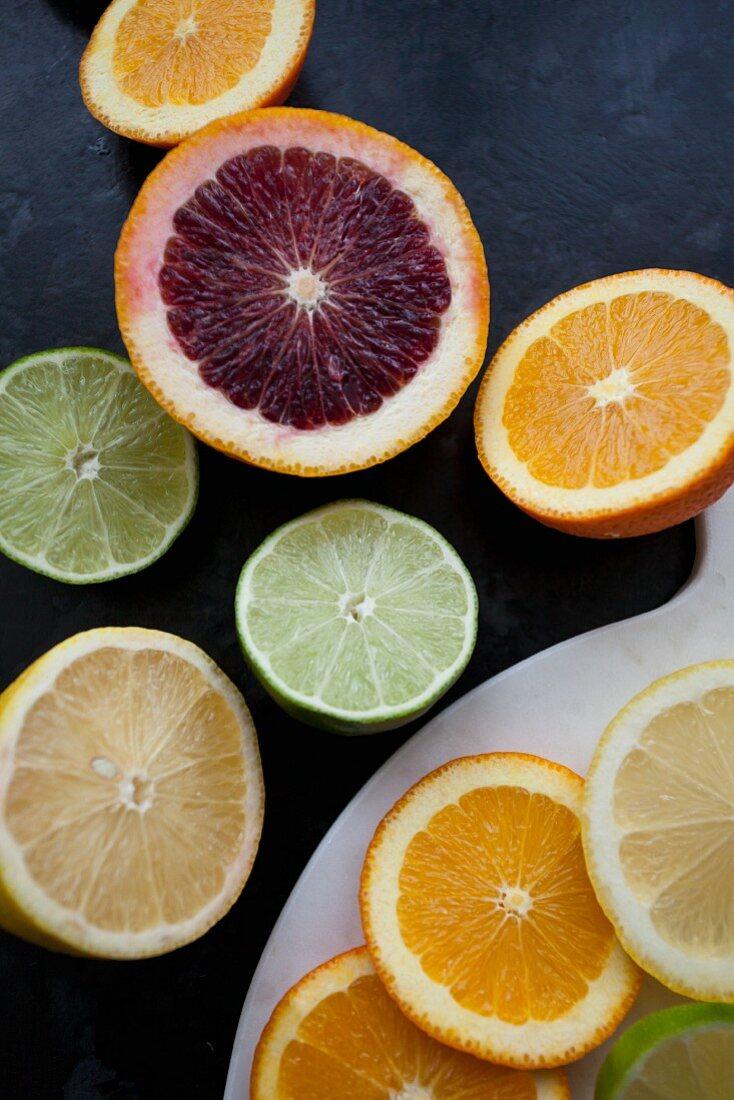 Verschiedene Zitrusfrüchte, in Scheiben geschnitten und halbiert (Draufsicht)