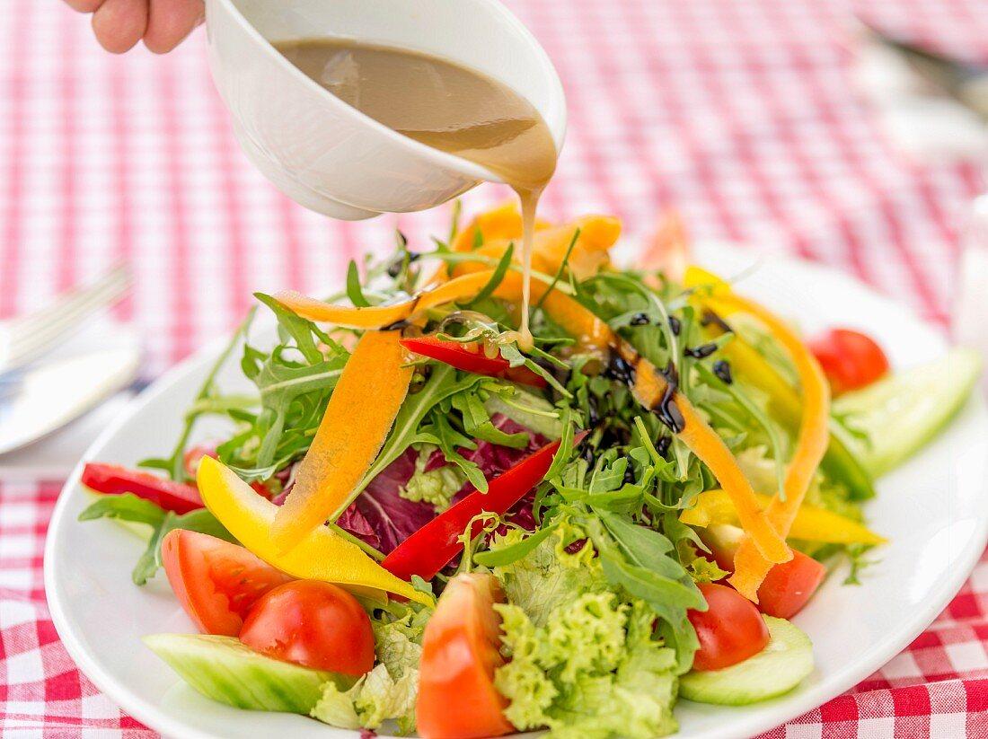 Gemischten Salat mit Rucola, Paprika und Tomaten mit Dressing begiessen