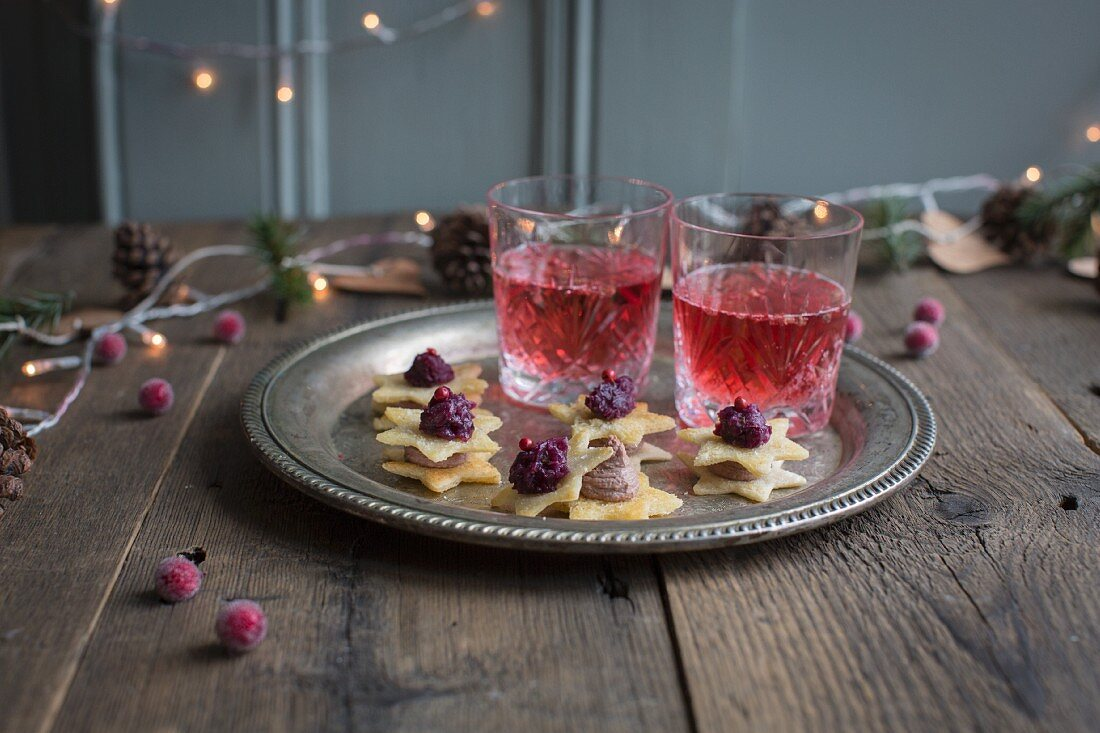 Tokyo Manhattan Cocktail made with cranberry juice serve with puff pastry stars topped with chicken liver pâté and red onion confit (Christmas)