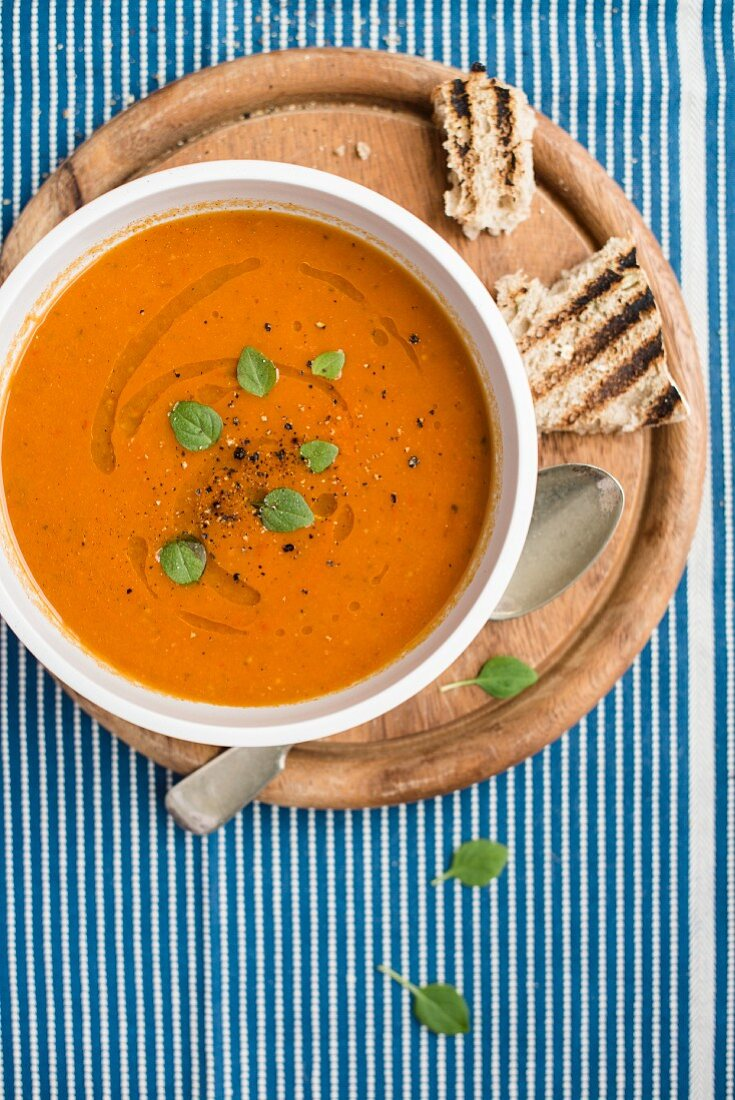 Cream of tomato soup with fresh basil and grilled bread