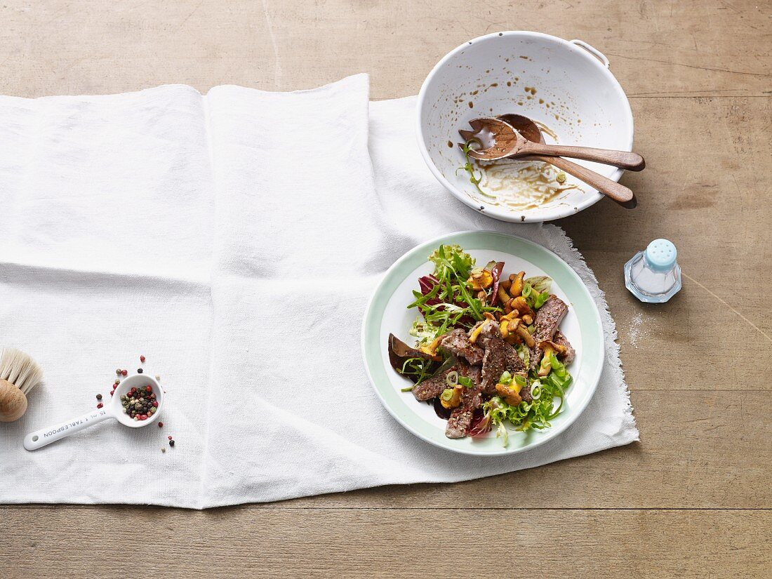 Mixed leaf salad with fresh chanterelle mushrooms and strips of steak (Paleo diet)