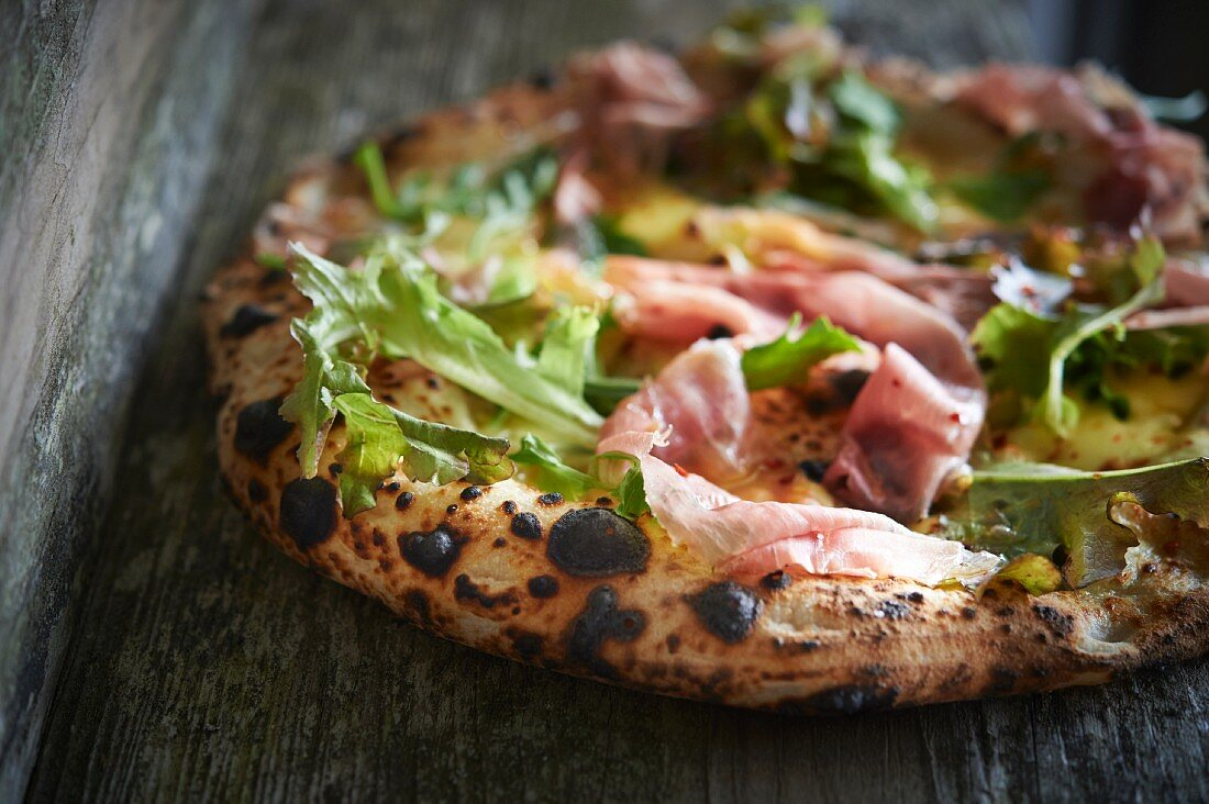 Pizza with prosciutto, mozzarella and rocket