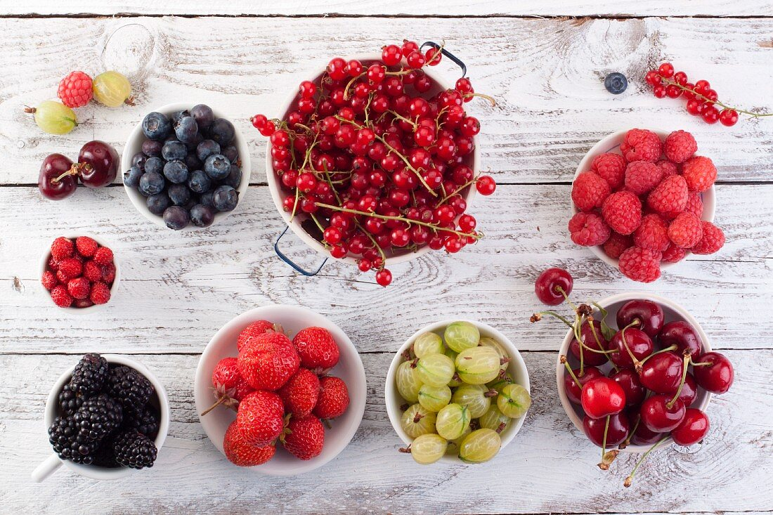 Fresh berries and cherries in bowls on a wooden surface