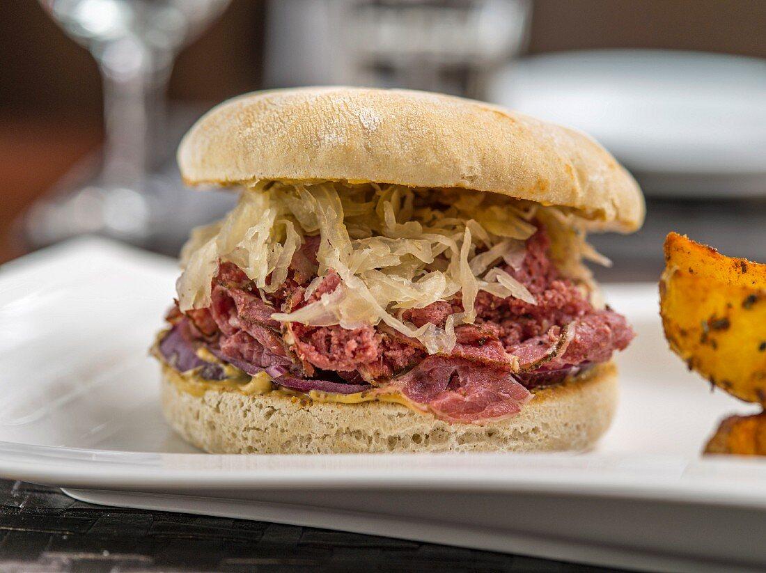 A pastrami burger with sauerkraut and a mustard sauce