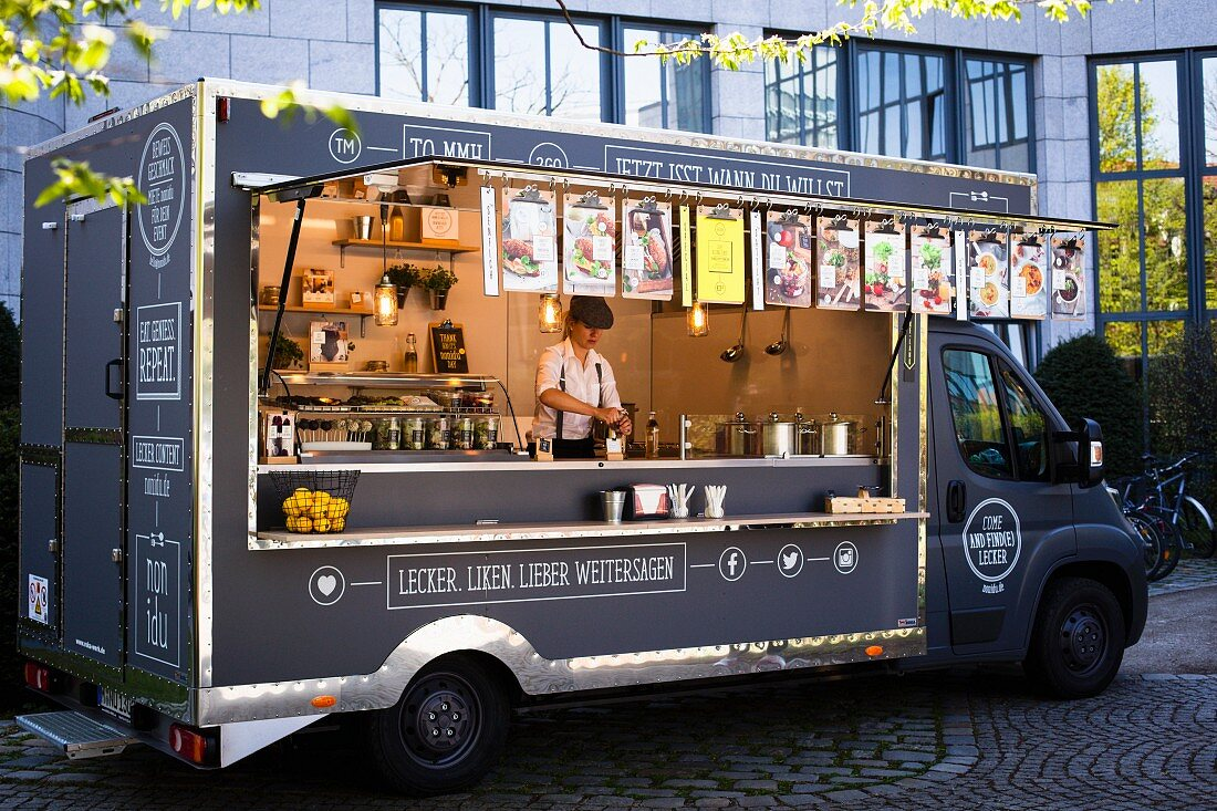 A food truck with various snacks in a courtyard