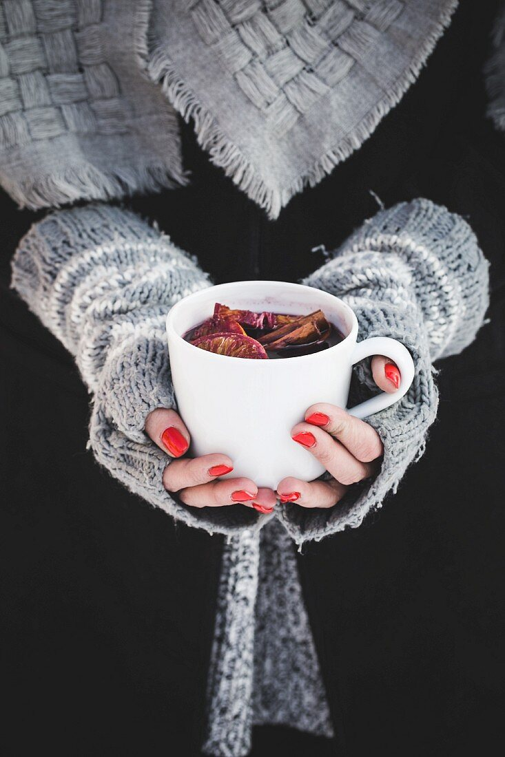 A woman holding a cup of mulled wine