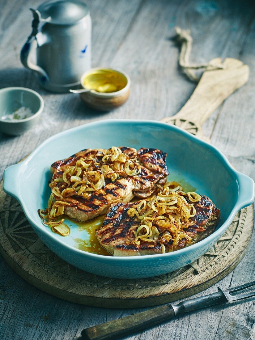 Grilled brewery-style pork steaks with onions