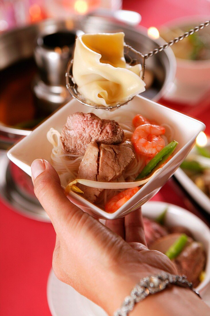 Food cooked in a pot-au-feu in a porcelain bowl