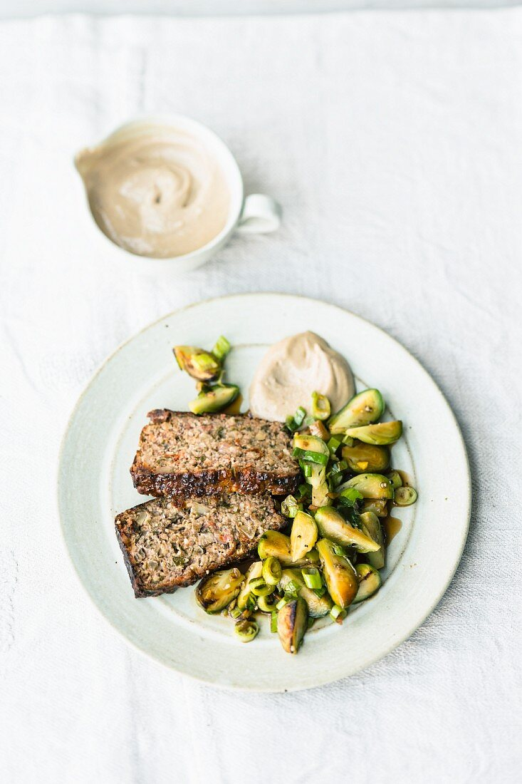 Roasted vegetarian nut and mountain cheese loaf with stir-fried Brussels sprouts and a tahini dip