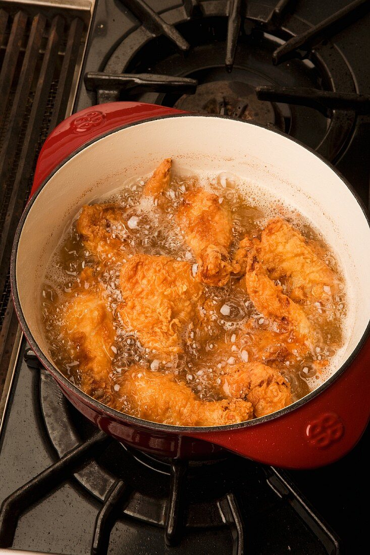 Chicken bits being fried in a pot