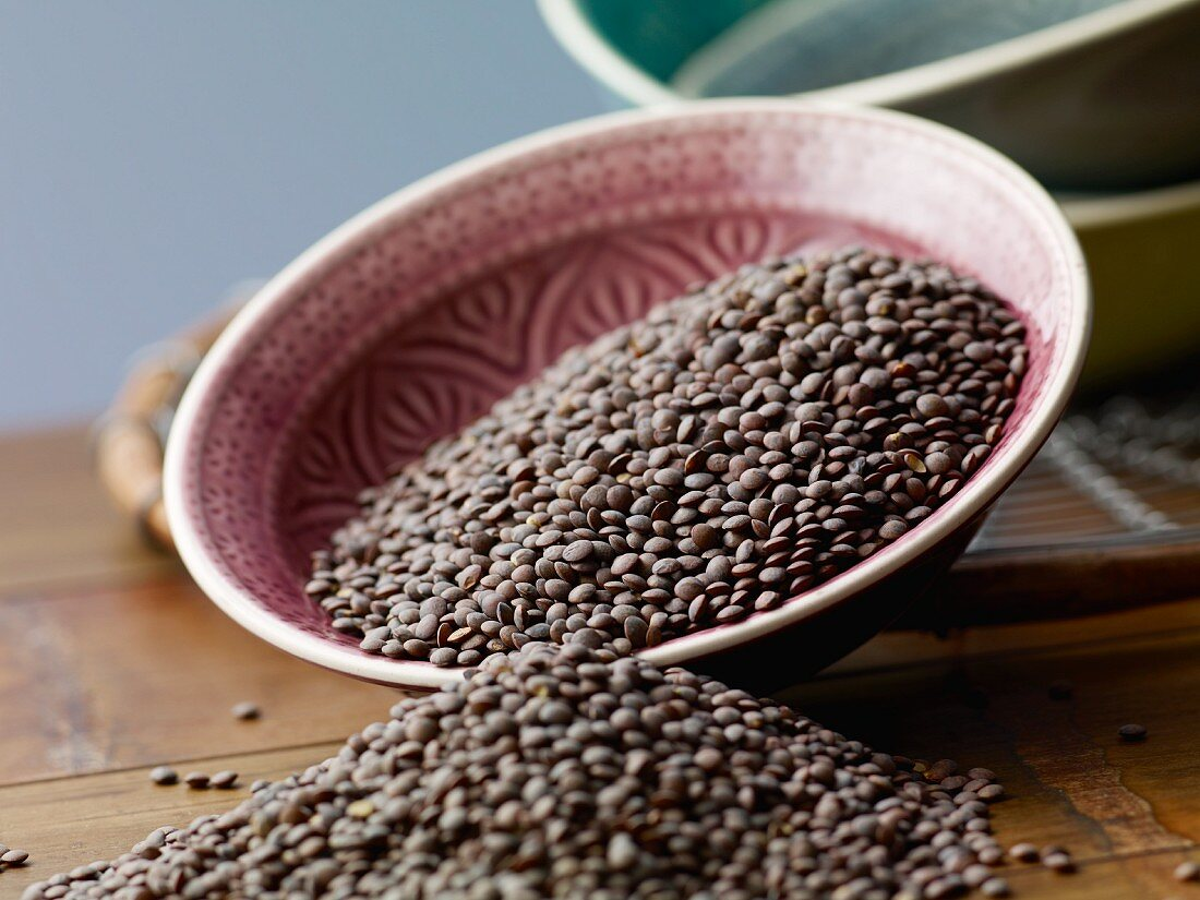 Green lentils in a bowl on a wooden table