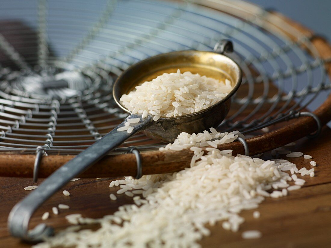 Rice in a ladle and on a wooden table