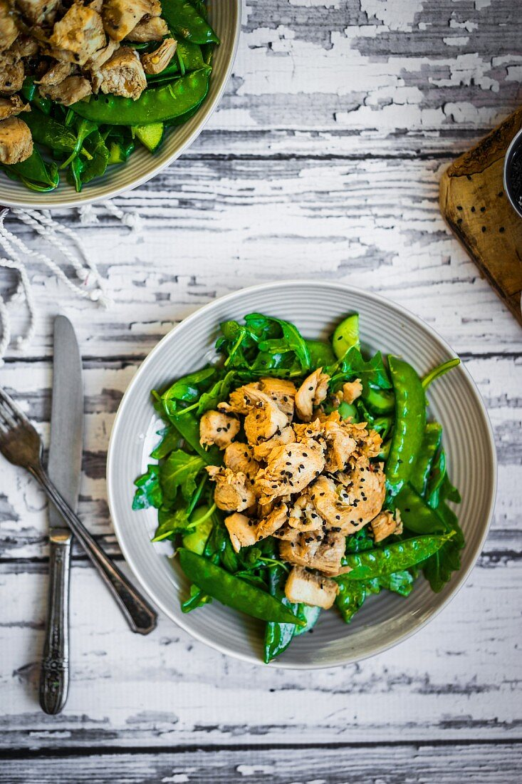 Grilled chicken with spinach, rocket and peas on rustic wooden surface