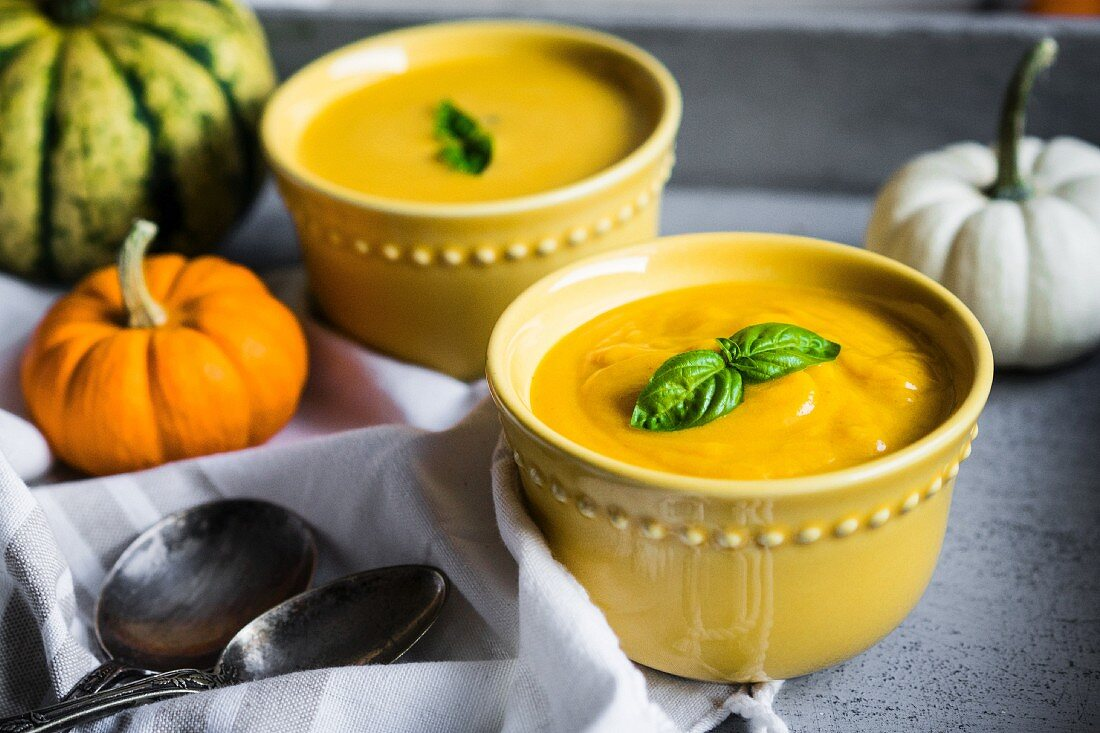 Cream of pumpkin soup with basil leaves