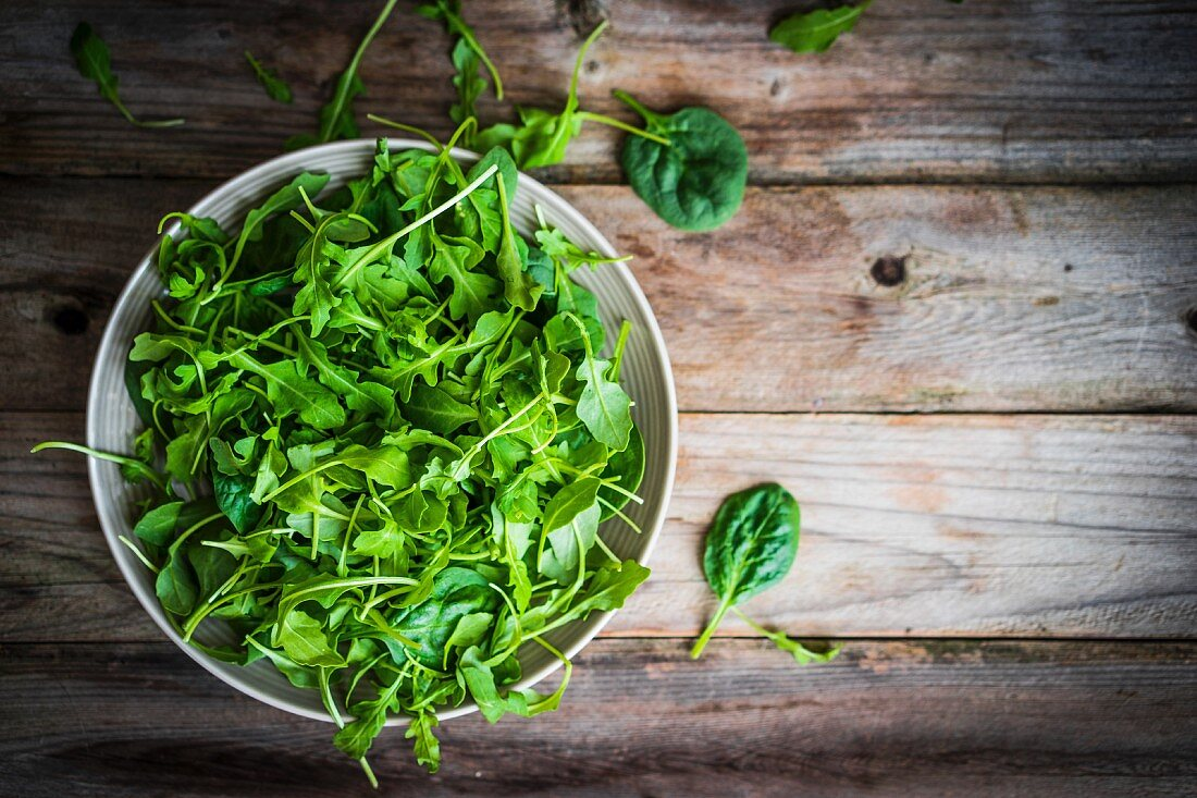 Fresh rocket and spinach salad on a wooden surface