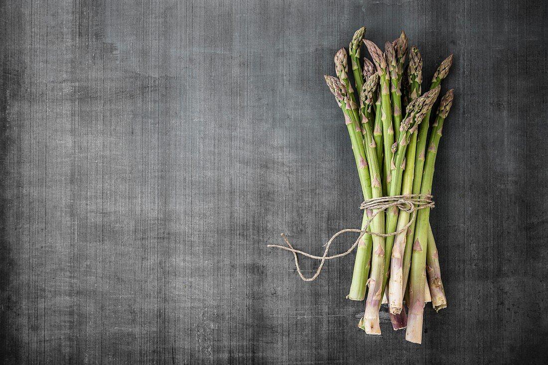 A bundle of asparagus on a grey surface