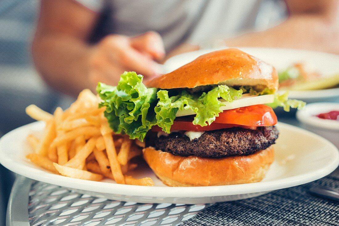 Hamburger mit Käse und Pommes frites auf Restauranttisch