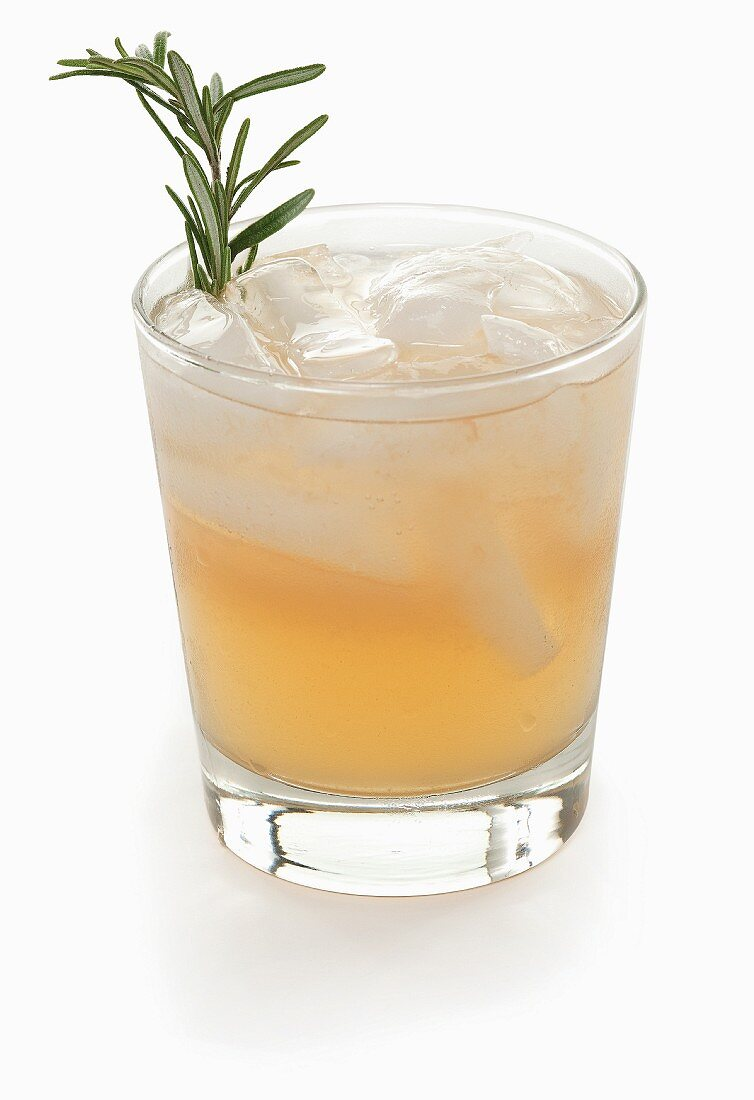 A cocktail with ice and rosemary on a white surface