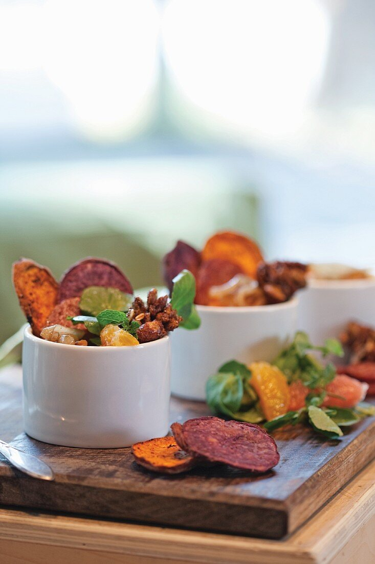A salad of dried vegetables crisps, oranges and nuts