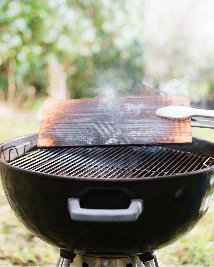 A cedar wood plank on a barbecue