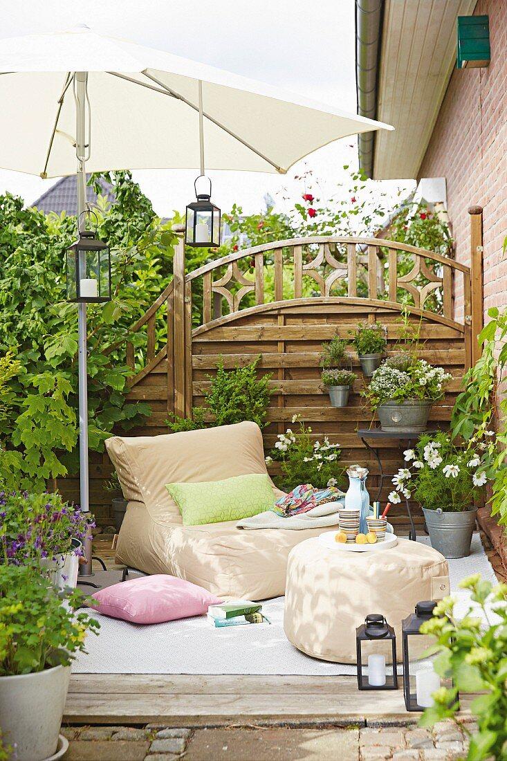 Sessel im Sitzsack-Style und Polsterschemel unter Sonnenschirm auf der Terrasse
