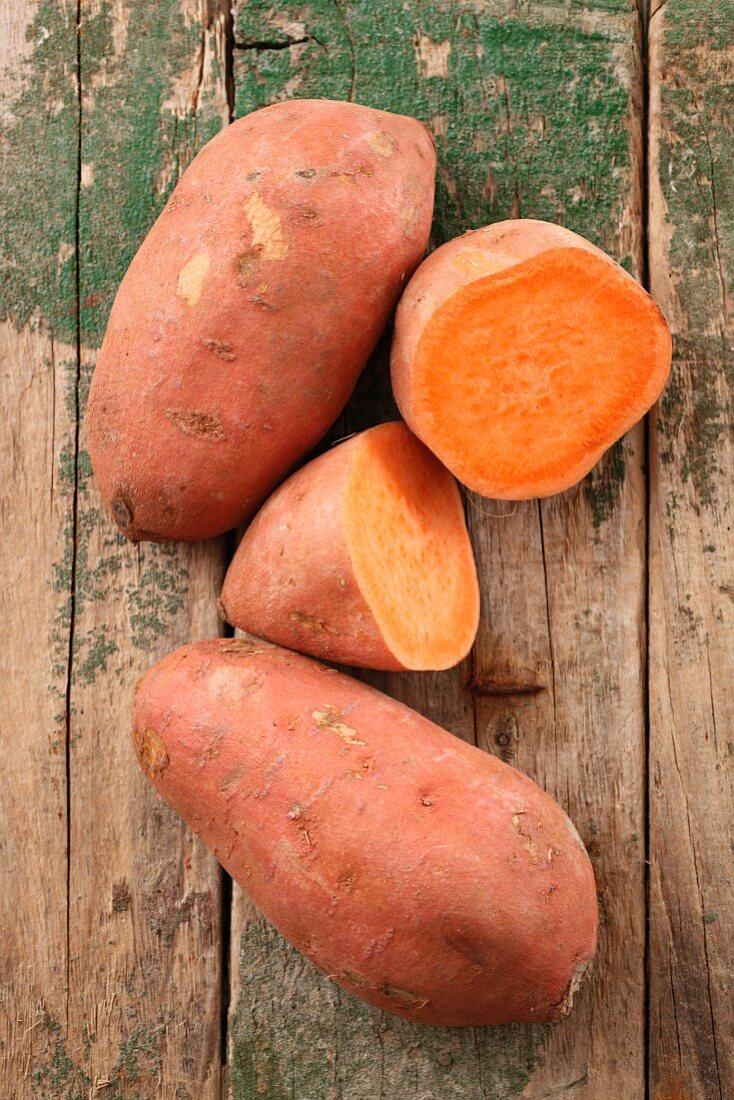 Sweet potatoes, whole and halved, on a wooden surface