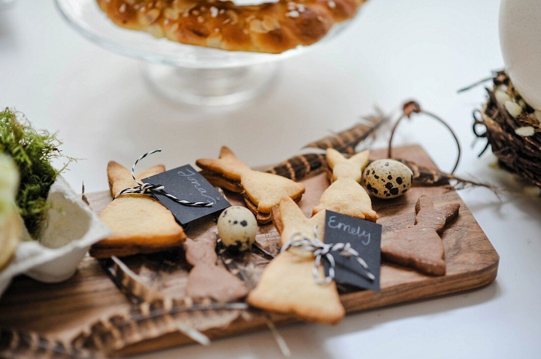Rabbit-shaped biscuits with name tags on wooden board