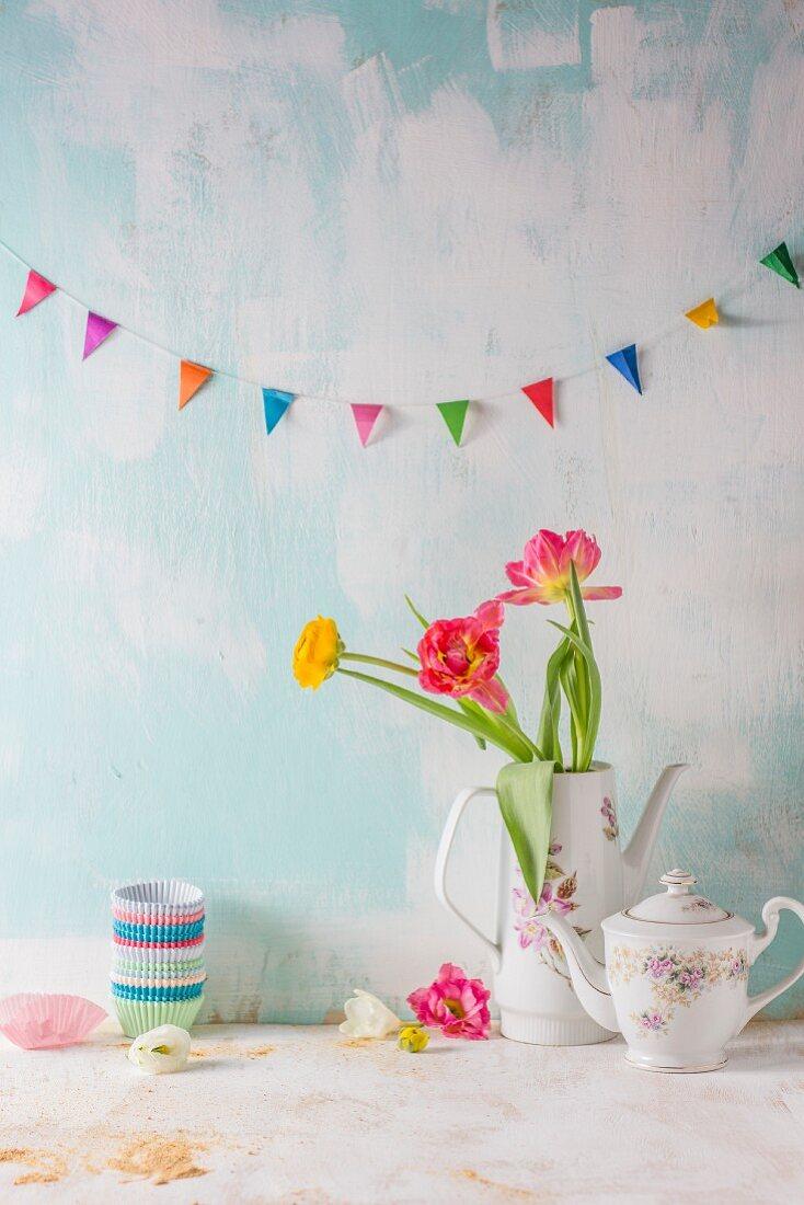 Stillleben mit bunter Wimpelkette und Blumenstrauss in Vintage-Kaffeekanne