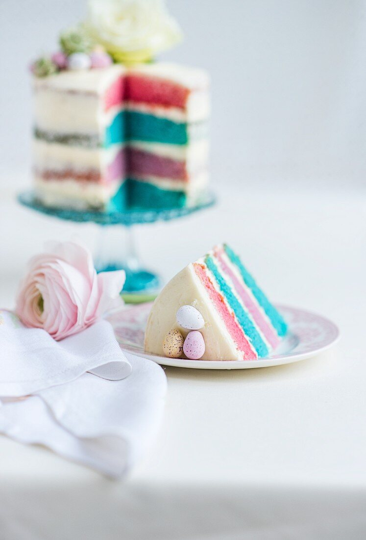 A four-layer rainbow cake with white icing, Easter eggs and flowers (sliced)