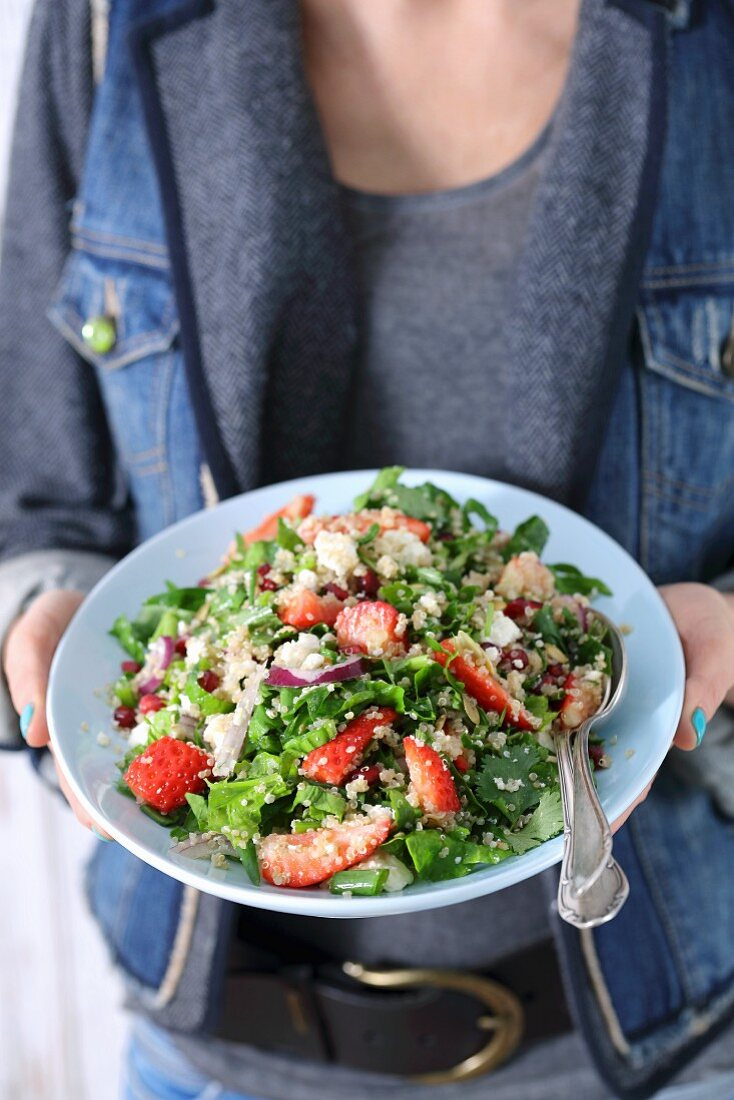 A plate of spinach and quinoa salad with strawberries and pomegranate seeds
