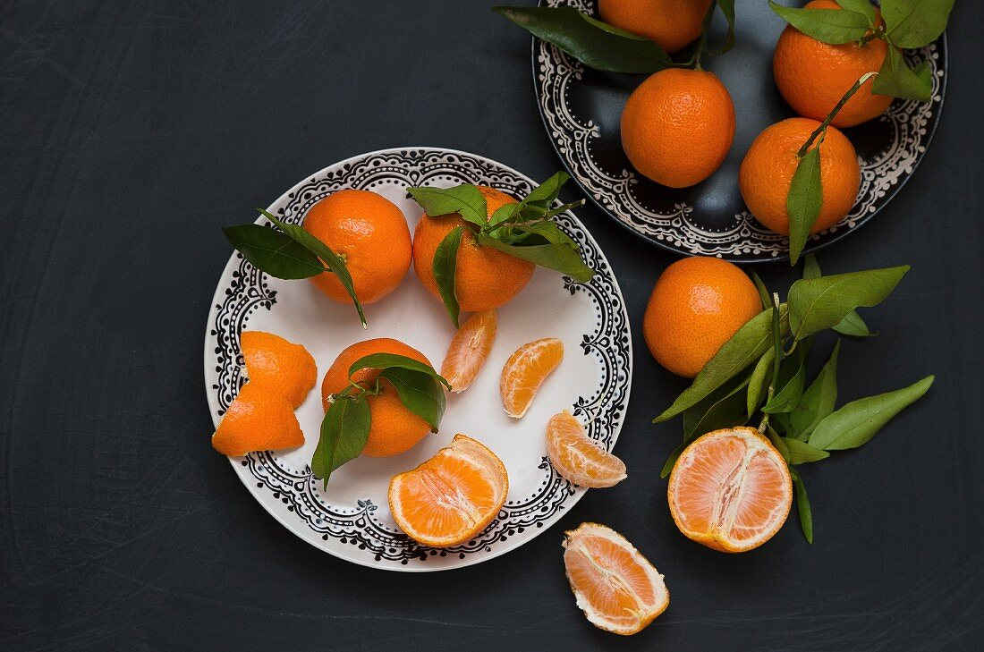 Oranges with stems and leaves, partially peeled