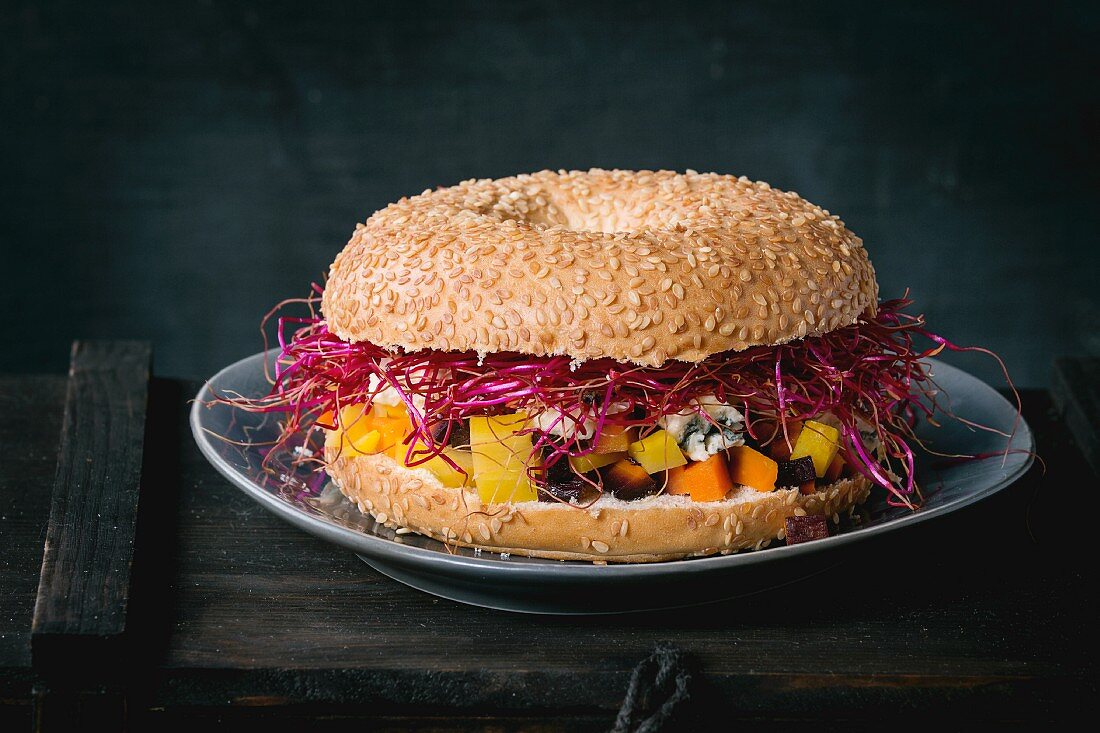 A bagel with carrots, blue cheese and beetroot sprouts