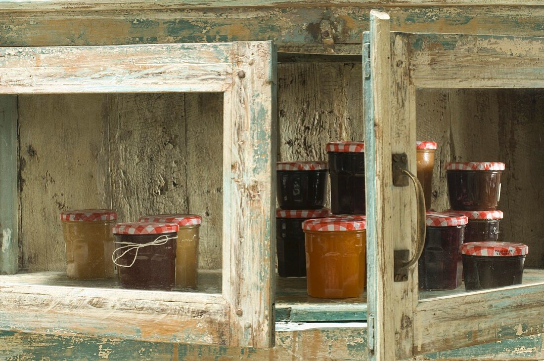 Jars of jam in rustic wooden cupboard