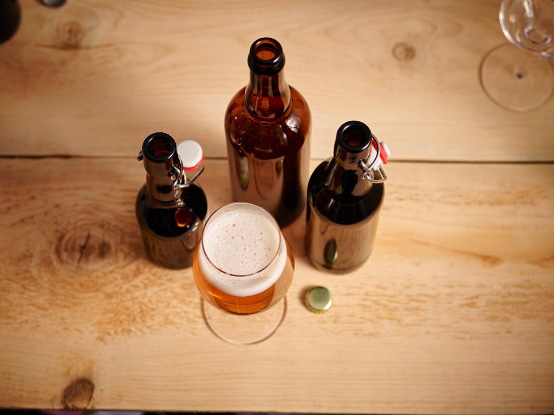 A glass of beer and three opened beer bottles