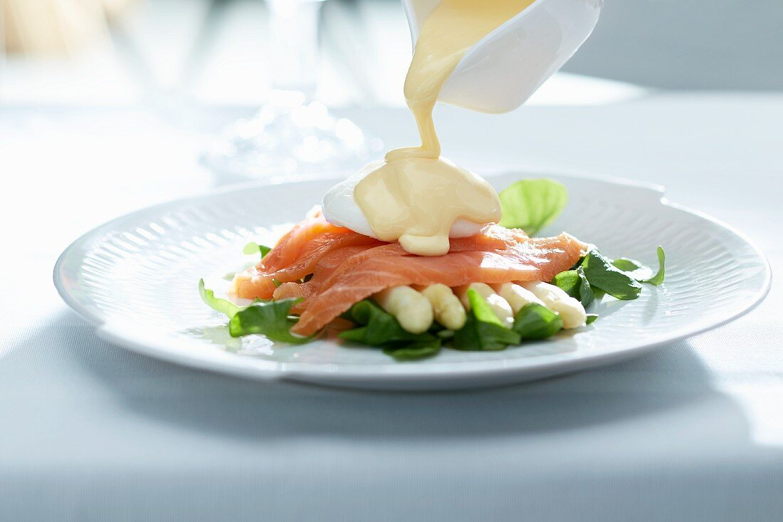 Hollandaise sauce being poured over white asparagus with salmon and poached eggs