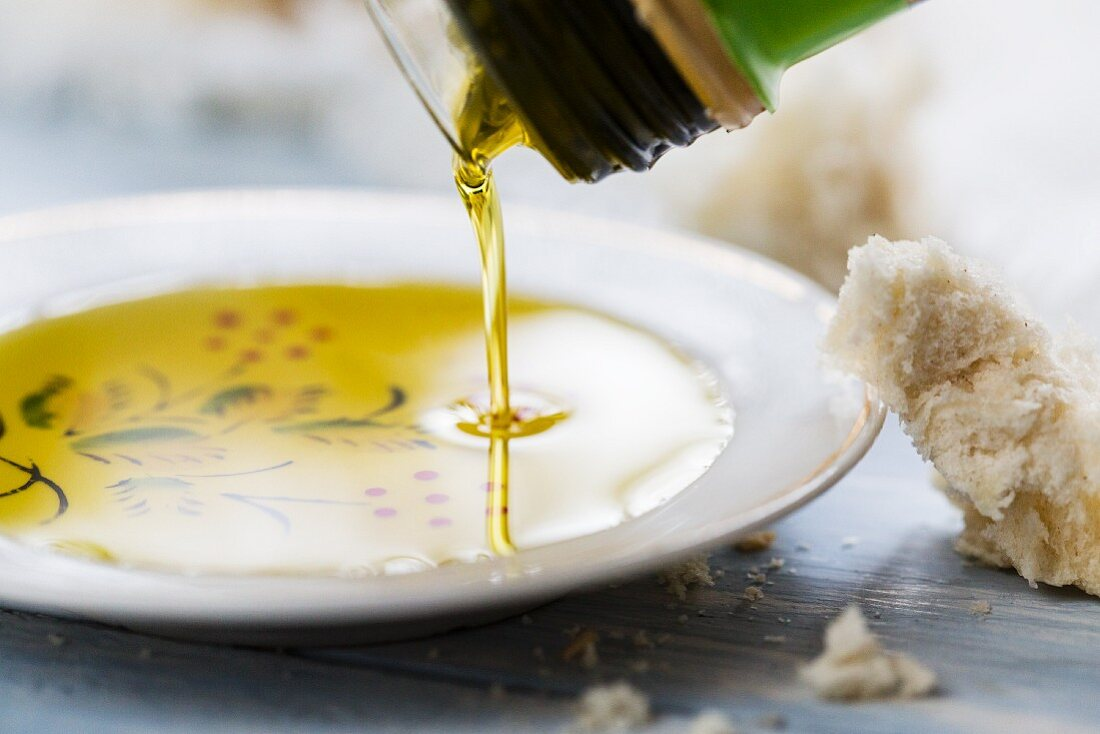Olive oil being poured into small dish for dipping