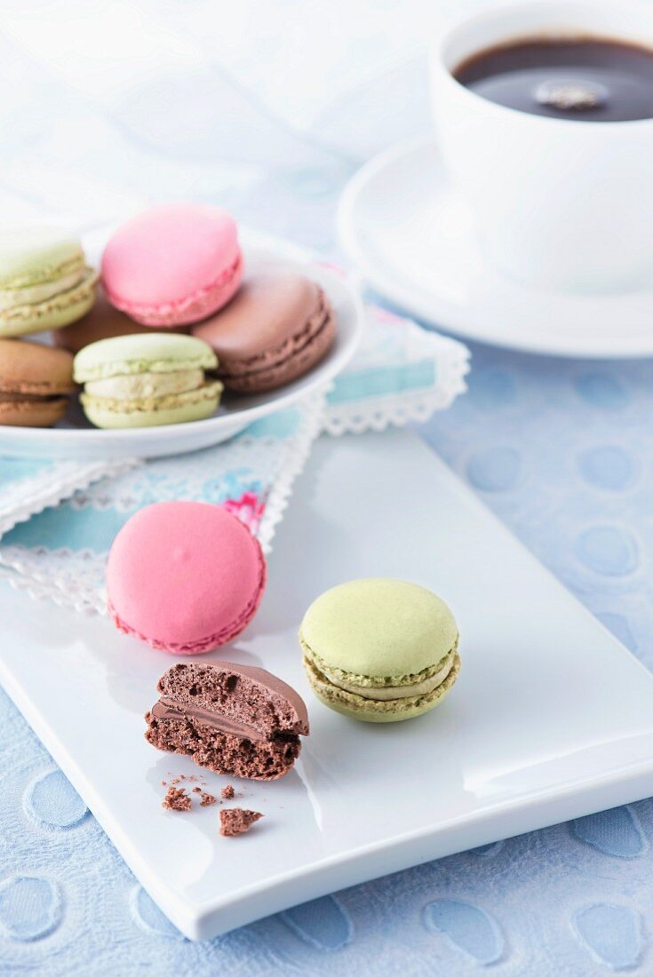 Macaroons on a white tray on a light blue surface with a cup of coffee in the background