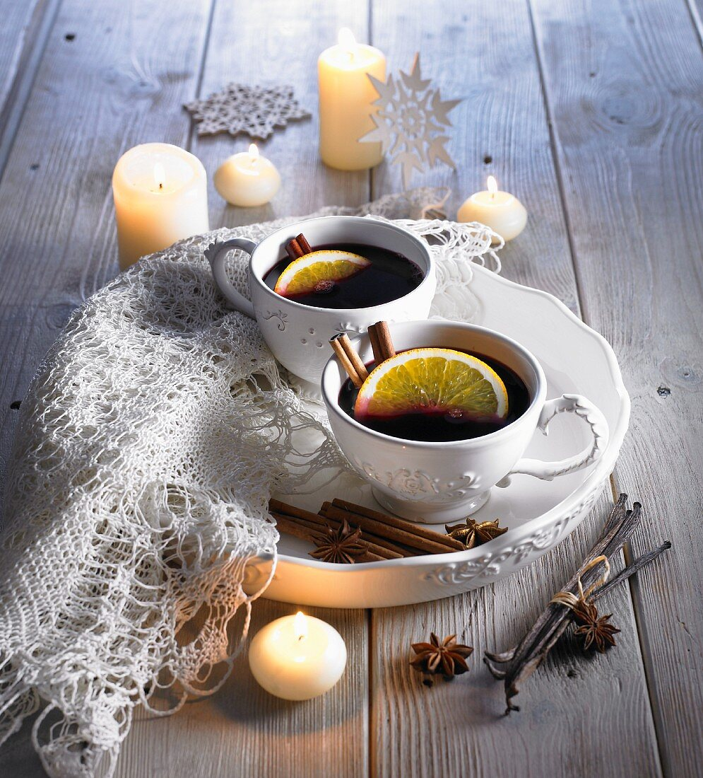Mulled wine in white cups by candlelight
