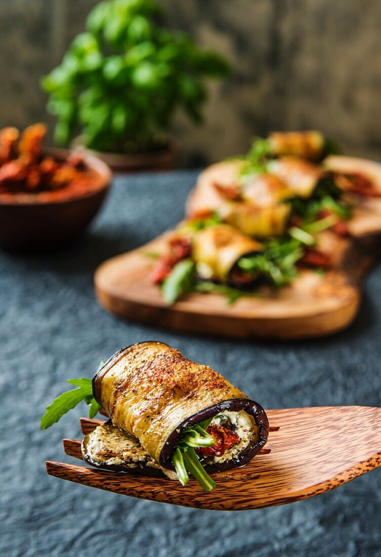 Aubergine rolls filled with sheep's cheese, rocket and dried tomatoes on a wooden fork and a wooden board