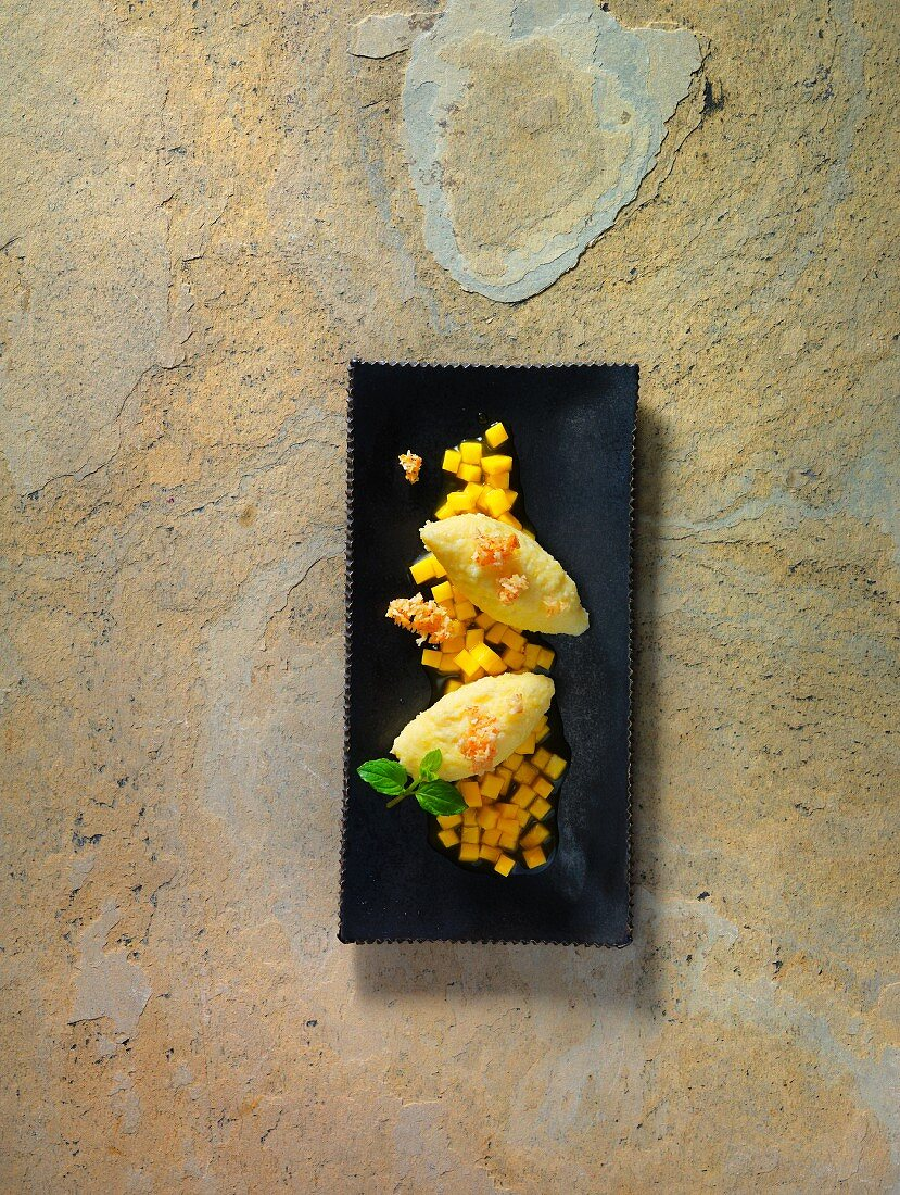 Quark dumplings with mango and passion fruit compote and coconut and honey crunch