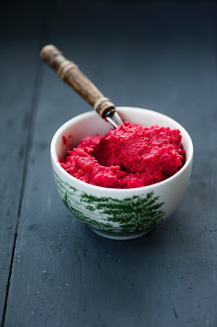 Beetroot and sweet potato mash in a bowl on a wooden surface