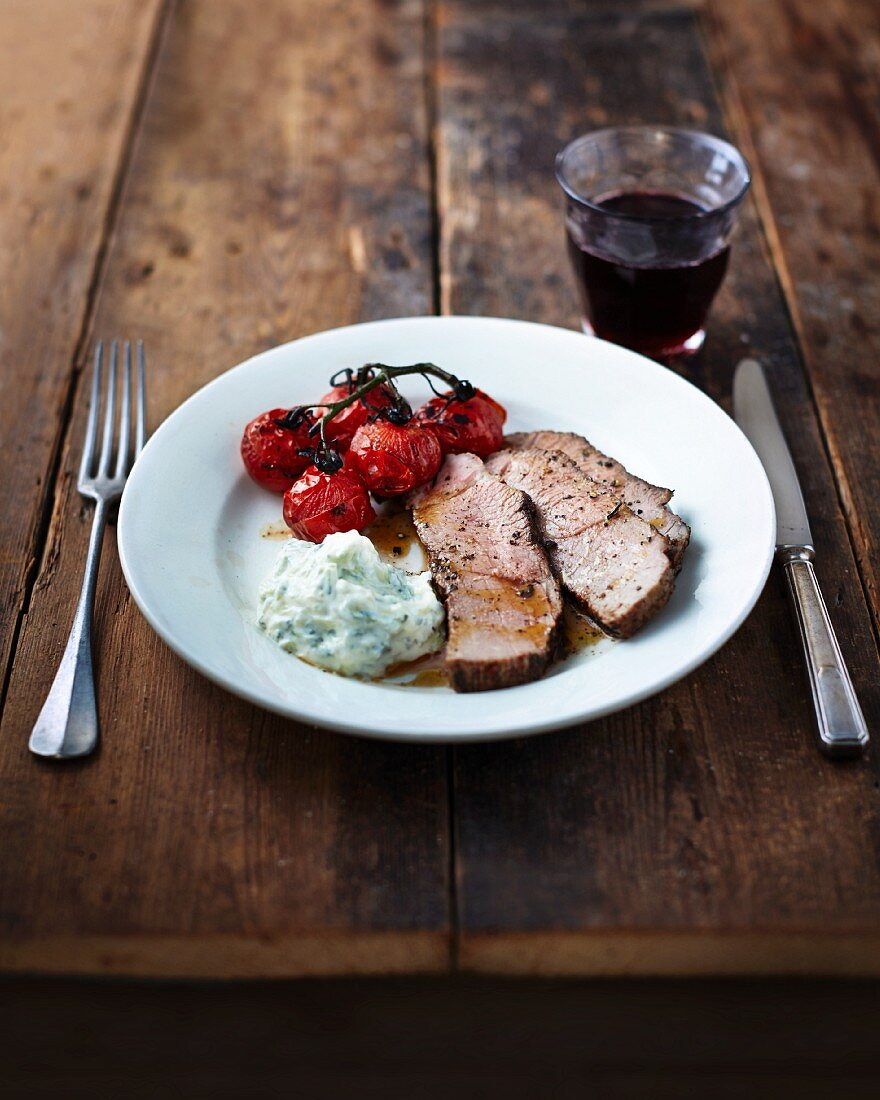 Roast beef with cherry tomatoes and mint and garlic sauce