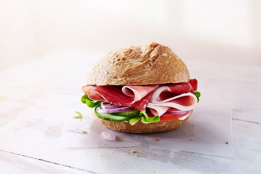 A rye bread role with ham, vegetables and lettuce