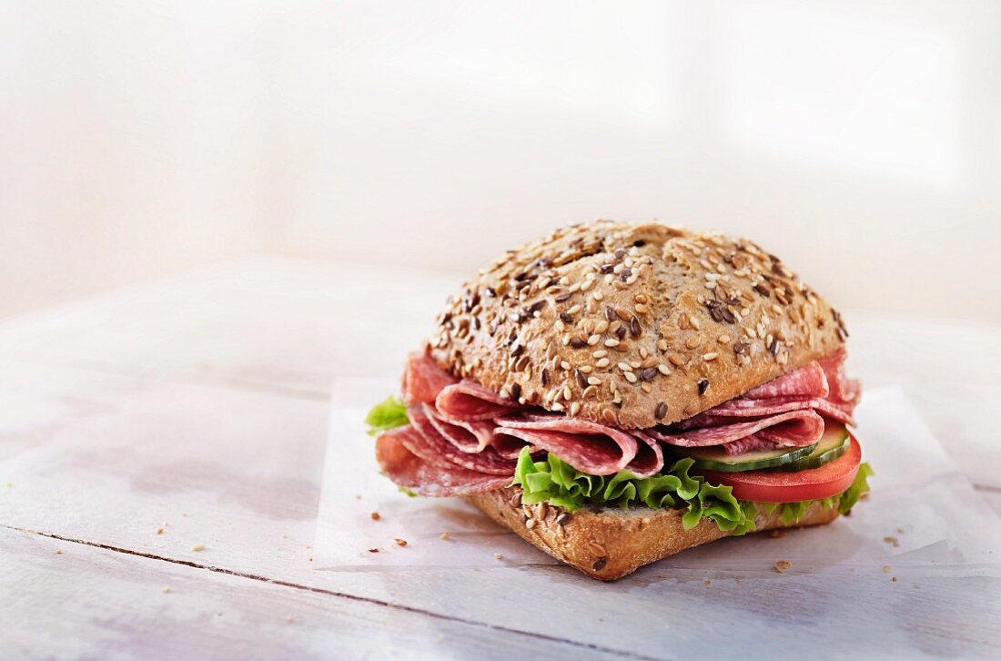 A wholemeal roll with salami, vegetables and lettuce